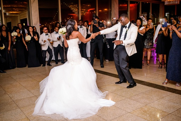 Bride in strapless wedding dress dancing with groom in white tuxedo jacket at wedding reception