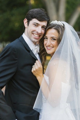 Woman in sparkling veil and man in tuxedo