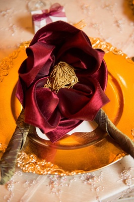 gold charger plate red napkin interesting configuration orange tassel jewish wedding reception