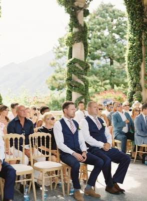 groomsmen and wedding guests at lake como wedding ceremony Villa del Balbianello greenery italy