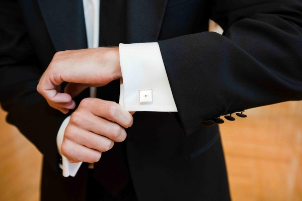 Groom wearing ivory cuff links with diamond border