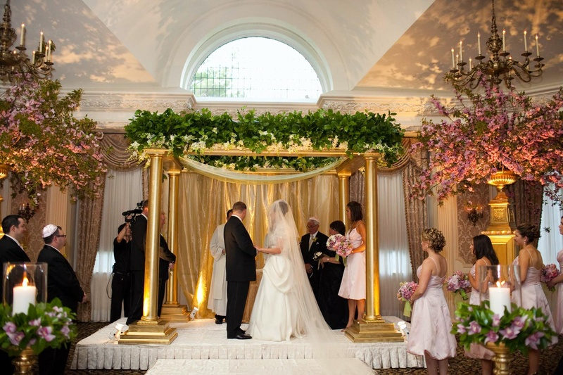 Bride in a Monique Lhuillier gown and veil stands with groom in a black tuxedo under a chuppah
