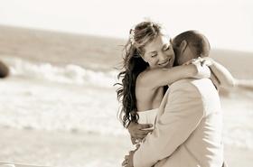 Bride and groom hug on beach near ocean