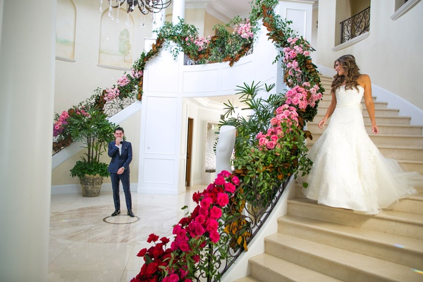 bride in strapless wedding dress long hair walking down staircase foyer of home