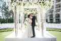 Tree branch chuppah with lucite structure white flowers greenery orchids roses kiss couple
