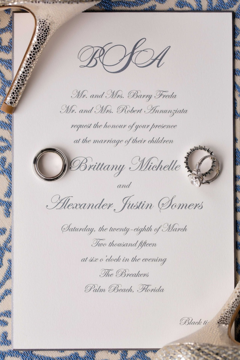 White black tie wedding invitation with grey calligraphy and monogram at top wedding rings resting