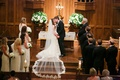 bride in vera wang, bridesmaids in lela rose, bride and groom kiss at altar