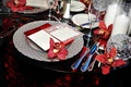 Red orchids and napkin on silver charger plates