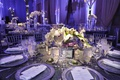 Metallic charger on grey reception table with white centerpiece