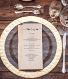 hammered gold-rimmed glass charger, farm table, silverware, wedding menu