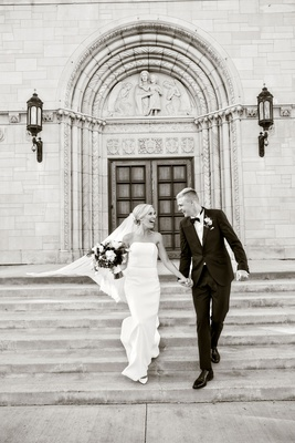 black and white photo of bride and groom running down church steps as husband and wife