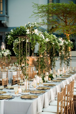 wedding reception decor gold chairs risers greenery white flowers candles tea lights