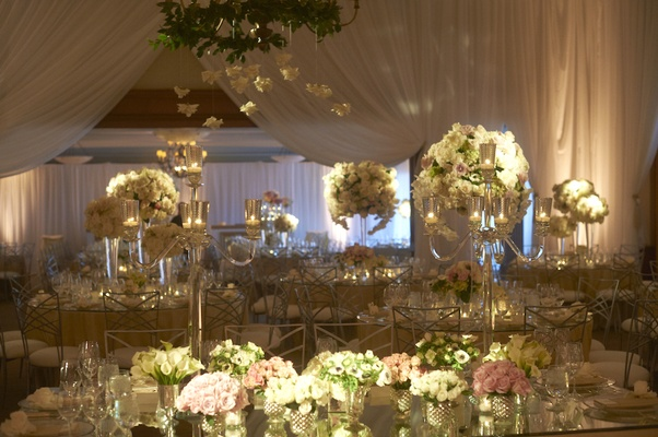 Mirrored tables topped with lush floral arrangements