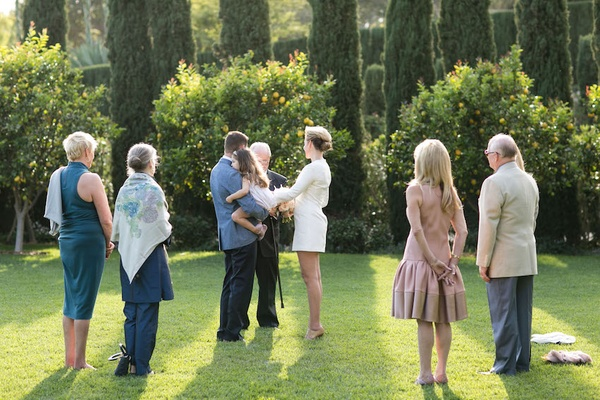 Bride in a mini Mod dress, groom in blue blazer, black pants with guests at outdoor ceremony