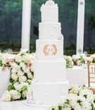 White wedding cake with sugar roses, vines, and couple's monogram crest in gold