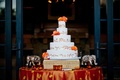 White wedding cake with golden swirls and fresh orange flowers