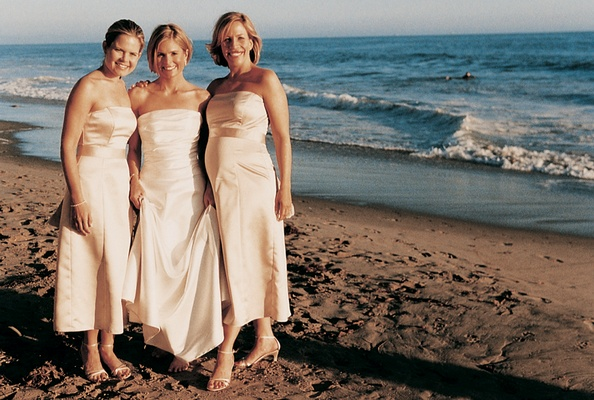 Bride stands on beach with her two maid of honor