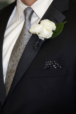 Groom in a black tuxedo, silver tie, boutonniere of three ranunculuses, green leaf