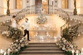 bride and groom walking down together grand staircase oheka castle flowers and candles on staircases