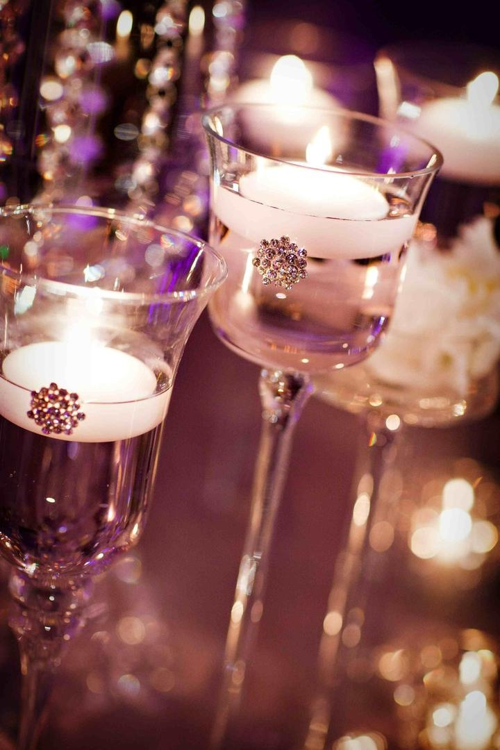 Glass candlestick with floating white candle and crystal brooch