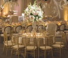 Wedding reception table with gold sequined linen, cut crystal vase with white hydrangeas, orchids