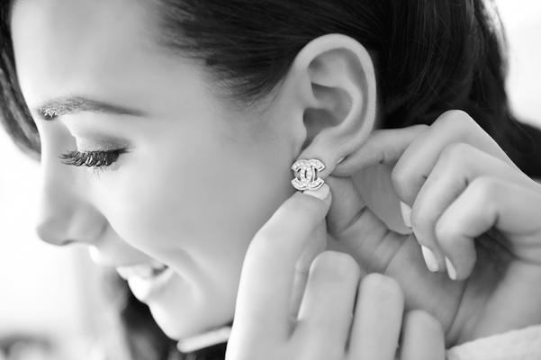 Black and white photo of bride securing Chanel logo earrings