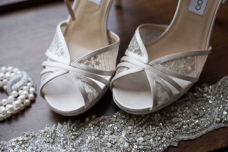 lace jimmy choo high heels sitting next to a delicate pearl necklace