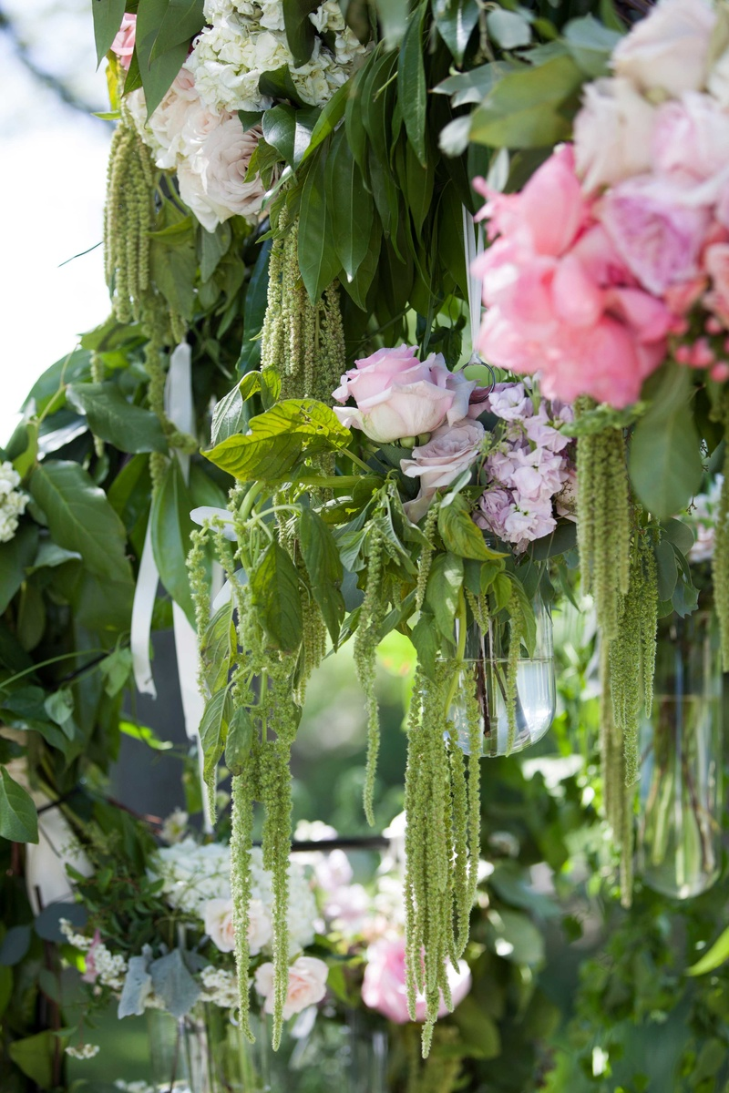 a close up snapshot of a couples verdant garden arch featuring dripping greenery and bright flowers