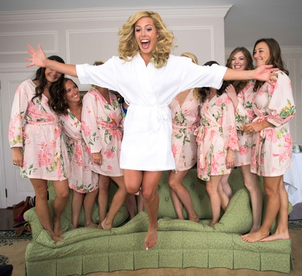 bride in white robe jumping from couch, bridesmaids in flower print pink robes