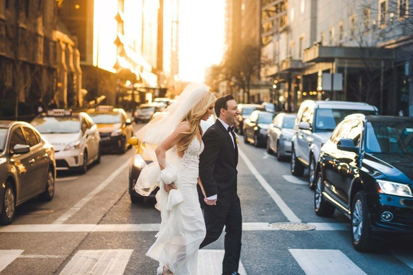 wedding portrait photojournalistic image bride in wedding dress and veil crossing street with groom