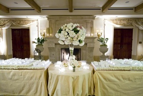 Wedding reception place cards set on stands decorated with white roses