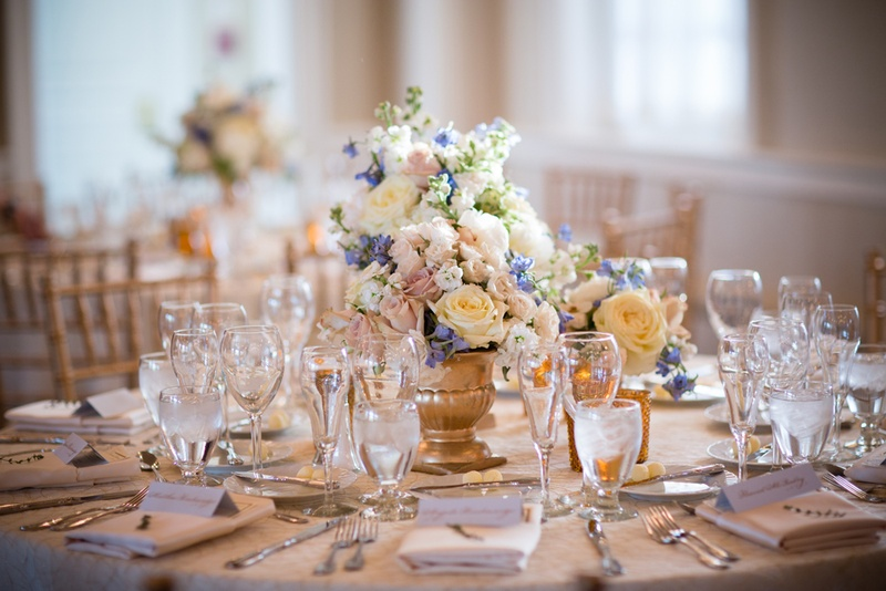 table decorated with short gold vase and pink, white and blue flowers