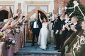 bride and groom celebrating exiting the church while bridal party waves streamers