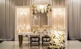 lacquer sweetheart table with two chandeliers on both sides candles tall candleholders orchid