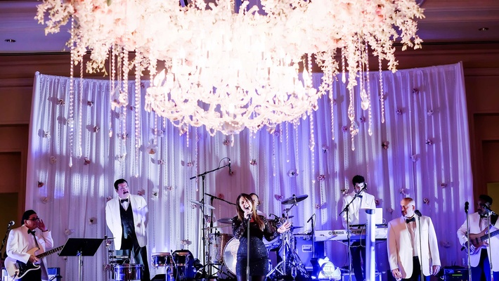 reception band performing floral chandelier singing classic dallas texas wedding purple blue uplight