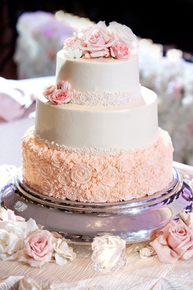 Wedding cake with flower rosette piping on base, buttercream frosting, fresh flowers on top