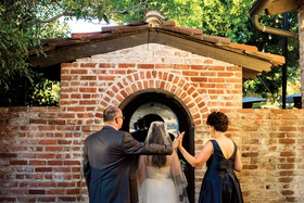 bride with wedding dress and veil going through brick wall jewish ceremony processional