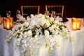 Cascading flowers over edge of white-covered table