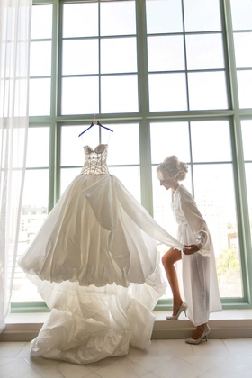 Bride getting ready with Ines Di Santo wedding dress hanging on window