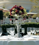 Silver candelabra topped with red roses and green orchids