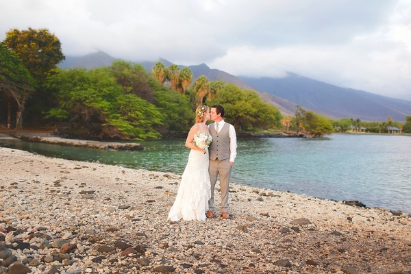newlyweds kiss on shores of maui, hawaii after destination wedding