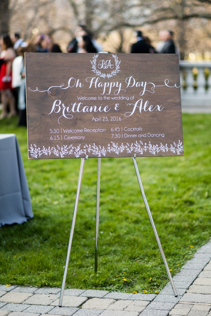 Wood sign with wedding itinerary calligraphy monogram and wedding date on grass lawn