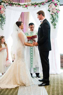 Bride and tall groom standing in front of Catholic priest