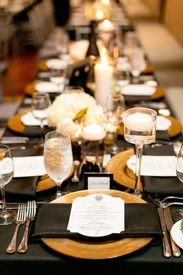 gold charger plate with black napkins and linens