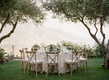 Round wedding table vineyard chairs ribbons with low centerpiece greenery ivory flowers grass trees