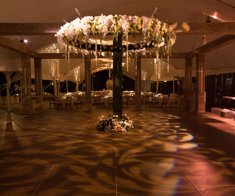 Lace lighting pattern on dance floor at rustic tent wedding