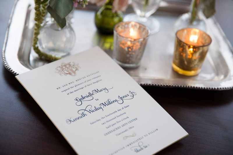 white wedding invitation with blue calligraphy and a gold monogram