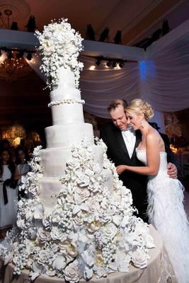 Bride in a strapless gown with groom in a black tuxedo cuts cake decorated with sugar flowers