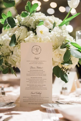 white itinerary with cursive font in front of white flowers and green leaves