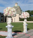 White hydrangea pink rose flower arrangement on column riser aisle with pink flower petals